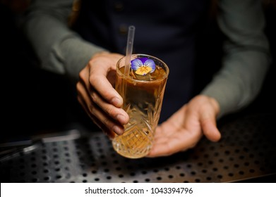 Bartender holding a sweet and fresh alcoholic cocktail decorated with a little purple flower on the bar counter