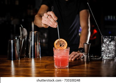 Bartender holding tongs in his hands adorns pink cocktail with an grapefruit slice. Barman at work, preparing cocktails