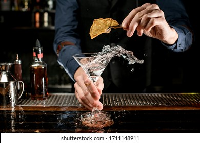 bartender holds beautiful transparent martini glass with splashing liquid and decorate it with plant using tweezers