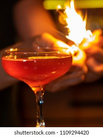 bartender ignites orange peel before serving cocktails