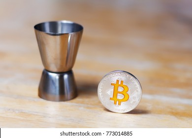 Bartender jigger and silver bitcoin on a wooden table
