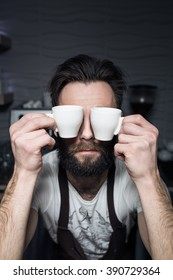 bartender keeps cups of coffee near face; bearded man wants to wake up in morning;