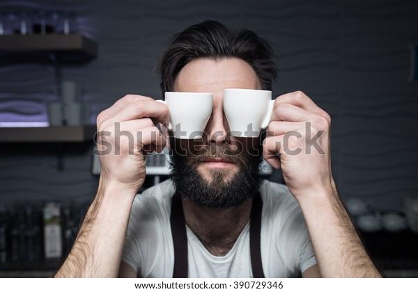 el barman mantiene tazas de café cerca de la cara; el hombre barbudo quiere despertar por la mañana;