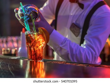 The bartender makes a cocktail at the bar, pours a glass of the shaker.