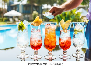 Bartender makes craft cocktails near the pool. Vacation, summer, holiday, luxury resort concept. Horizontal