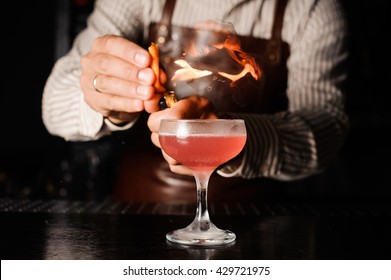 The bartender makes flame above cocktail