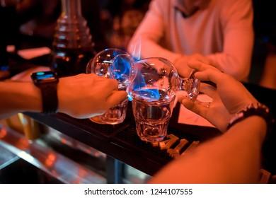 Bartender makes hot cocktail sambuca