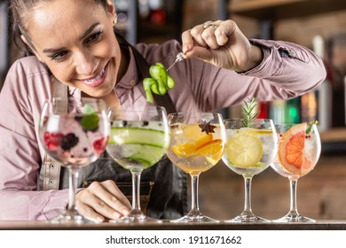 Bartender makes summer refreshing gin tonic cocktails on a bar.