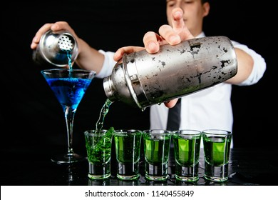 Bartender making alcohol shots at the bar Barman preparing green and blue shots for a party. Expert barman mixing colorful cocktails at nightclub. Cocktail shooter at the black bar counter.