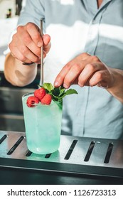 Bartender making alcoholic cocktail in the bar, spirits drink on bar table. Summer cocktail