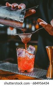 Bartender making alcoholic cocktail in red color, metal jigger and bar environment