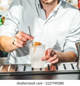 Bartender making alcoholic cocktails in bar, spirits drink on table.