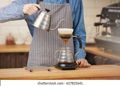 Bartender making alternative coffee using manual drip brewer, pouring water.