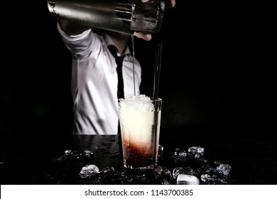 Bartender is making cocktail at bar counter. Barman mixing drinks at the night club. Bartender preparing cocktail. Cocktail on a black background.