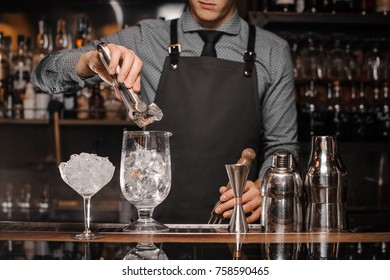 Bartender making a cocktail with help of the bar equipment arranged on the bar counter