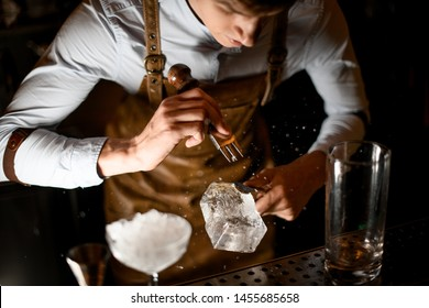 Bartender making a crushed with a special instrument on the bar counter in the dark blurred background