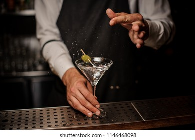Bartender making a fresh and strong martini summer cocktail with a green olive and salt
