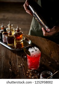 Bartender making a red cocktail in a bar, vertical
