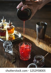 Bartender making a red cocktail in a bar, pouring cocktail in a glass, vertical close up