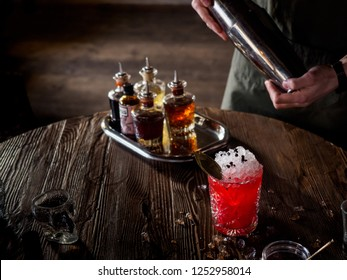 Bartender making a red cocktail in a bar