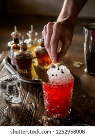 Bartender making a red cocktail with bay leaf in a bar, vertical close up