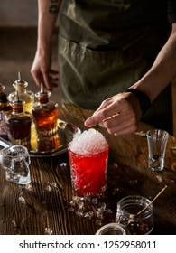 Bartender making a red cocktail with bay leaf in a bar, vertical