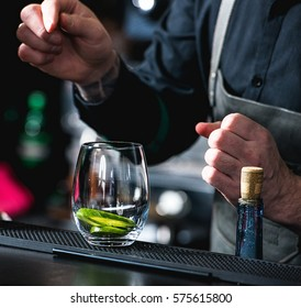 bartender making refreshing coctail with cucumber isolated on a bar background