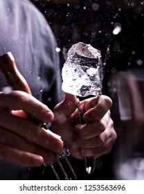 Bartender making refreshing coctail on a bar background. Dark moody style. Ice in tha glass
