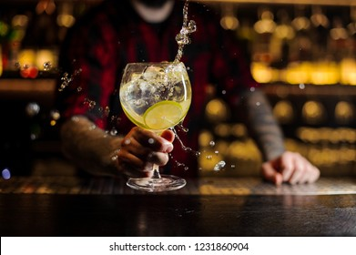 Bartender making splash of a delicious Gin Tonic cocktail with lime slices on the steel bar counter on the blurred background
