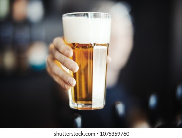 Bartender Man Stretches Out a Glass of Beer To Customer. Offers Alcoholic or Non-Alcoholic Drink. Concept OF hospitable Service.