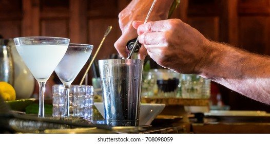 Bartender mixes a cocktail. Close up in a bar setting. Chilled frosty glasses.