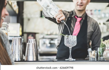 Bartender mixing cocktail in a trendy crystal glass with aromatic herbs  - Young people waiting for drink at party disco bar - Focus on glass - Nightlife,alcohol,fashion,music concept - Retro filter