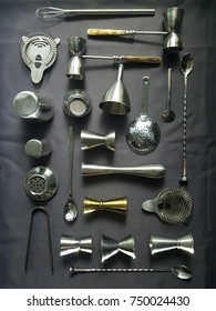 Bartender and mixology tools resting on a dark grey table top