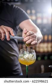 Bartender muddling lime to make a cocktail