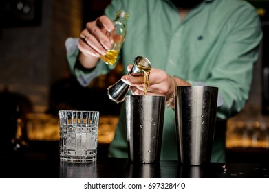 The bartender no face pours alcohol in a bar. Two shakers, a bottle, a jiger and a glass with ice