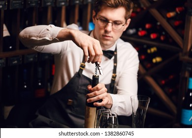 Bartender opening a wine bottle with corkscrew in restaurant with wine shelves.