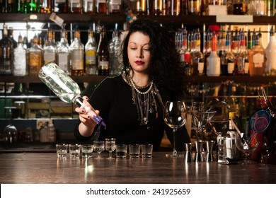 Bartender  pouring alcohol into shot glasses