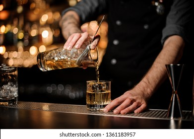 Bartender pouring an alcohol from the measuring glass cup through the strainer to the cocktail on the bar counter in the blurred background