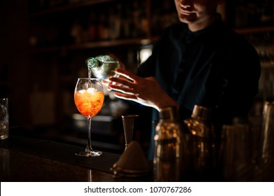 Bartender pouring an alcoholic drink from a bottle into a cocktail glass on the bar counter