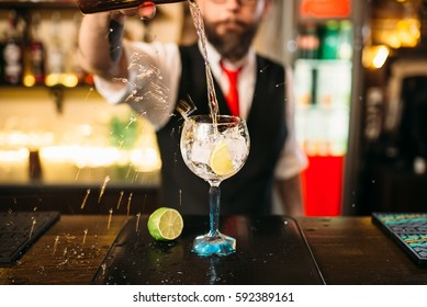 Bartender pouring alcoholic drink in glass