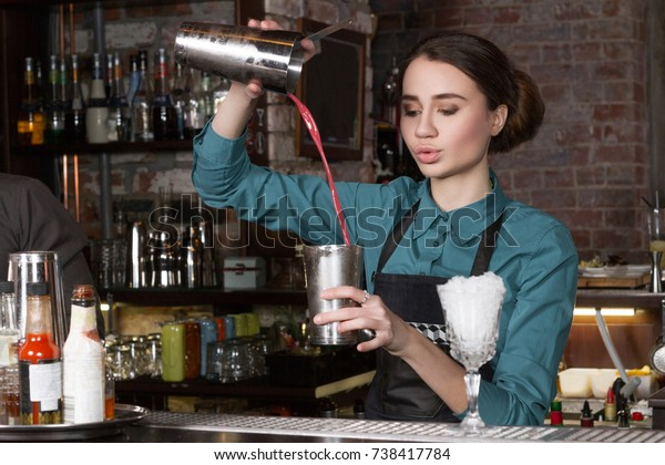 Bartender pouring alcoholic drink with a glass in a bar