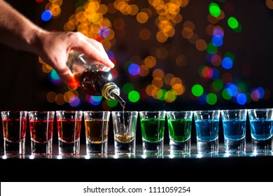 Bartender pouring alcoholic drink into small glasses on bar. Colorful cocktails at the bar. Colorful shots at the club. Alcoholic drink in different colors. Nightlife scene. Shots at the bar table.