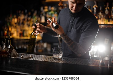 Bartender pouring an alcoholic drink making a cocktail from the steel jigger to the glass on the bar counter