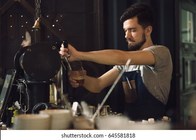 Bartender pouring beer to glass in bar
