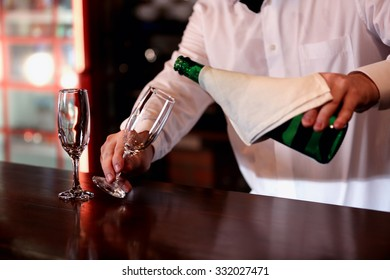 Bartender pouring champagne into glass, close-up
