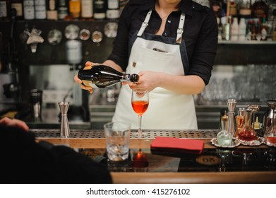 Bartender pouring champagne into glass, close-up no face