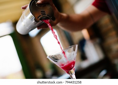 Bartender pouring cocktail into the glass