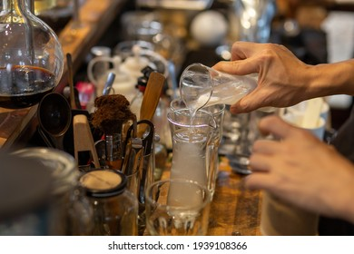 The bartender is pouring the coconut water mixed with the coconut pulp into a clear glass. To mix drinks for customers in coffee shops