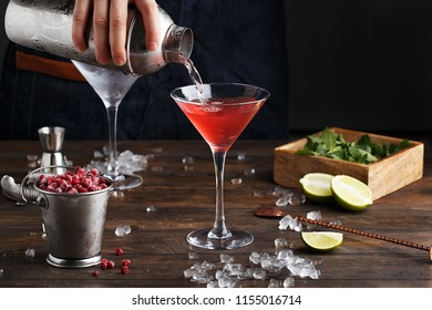 Bartender pouring Cosmopolitan cocktail in martini glass