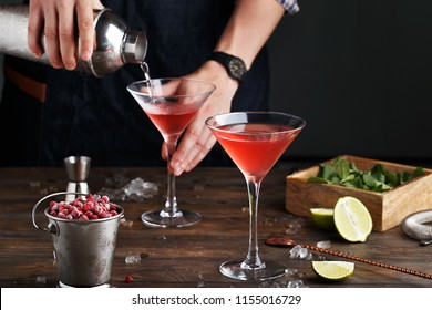 Bartender pouring Cosmopolitan cocktail in martini glass